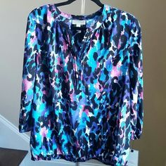 Beautiful Dana Buchman Splitneck Top Let this silky Dana Buchman top fulfill your fashion needs. A colorful, printed design, pleated neckline create a stylish look you'll love. Elastic hem and cuffs, 3/4 leght sleeves. 100% Polyester. Dana Buchman Tops Blouses