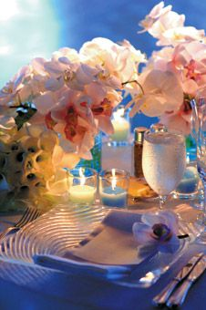 """""""clean, minimalist vibe... trios of low vases with all-white arrangements of orchids, calla lilies and hydrangeas."""""""