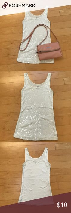 """White Sequined Tank Fun little sequined tank that is great to dress up or down. Very comfortable with no scratching from the embellishments. Sequins are surprisingly versatile, and I wore this top with denim and even under blazers.   Preloved condition. There is some pilling under the arms from wearing it under a navy blazer. Also missing about 5 sequins at the hem, but not noticeable at all.   25"""" long and 13.25"""" across with lots of stretch. Old Navy Tops Tank Tops"""