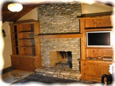 would LOVE to re-do our fireplace with a river rock surround like this...and those built-ins are pretty awesome too