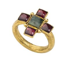 Early Christian Gemstone Ring.   Date: 4th–5th century CE. Culture: Roman. Medium: Gold, garnets, and emerald. Dimensions: Bezel 3 x 17 x 18 mm.; circumference 55 mm.; weight 4.2 gr. Classification: Metalwork-Gold.  In the Metropolitan Museum of Art, New York.