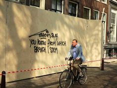 https://flic.kr/p/FKuqnc   2015.04 - Amsterdam photo of street-art & light - A wall-writing, a cyclist and shadows on the wooden fence, street Keizersgracht; a geotagged free urban picture, in public domain / Commons CCO;  city photography by Fons Heijnsbroek, The Netherlands   Amsterdam photos, street-art and light - A man on the bike and a wall-writing of the famous Dutch, and mainly Amsterdam, street-artist Laser 3.14. Location is in the city-center at the canal-street Keizersgracht…