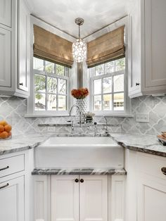 Fabulous Kitchen With Corner Farmhouse Sink Paired Gooseneck Faucet Below A Pair Of Small Windows Dressed In Woven Shades Illuminated By Capiz Shell