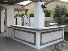 This Mediterranean outdoor kitchen features a large stainless steel grill and a split-level BBQ counter and L-shaped bar serve bar made of cast concrete imbedded with recycled beer bottle glass. Travertine tile trim framed in Old World vintage tile liners matches the detailing on the adjacent outdoor shower.