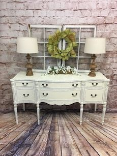 I mean seriously we are speechless over here . We think you Nesters would agree .. this stunner speaks for herself!  Vintage Buffet features Solid Wood, Dovetailed Drawers, 4 gorgeous ornate legs with detail to die for ! She was painted in 2 coats of Pure White with a wash of Old White, Distressed & sealed with clear wax! She's flawless! In Mint condition! Use her as your TV stand, Dining Room Buffet, Kitchen Island or even a double sink Bathroom Vanity!! Repurposing possibilities are...