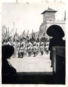 1944- Carrying national banners, members of the China Youth Corps pass the old city wall on their way to drill in Chengtu, China.