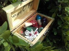 A wooden box contains a scroll of protective spell, glass vials with magic…