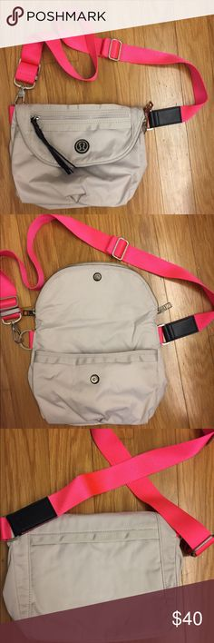 """Lululemon Festival Bag. Dune/Deep Coal. Lululemon Festival Bag in Dune/Deep Coal. The strap is  Flash, which is like a neon pink/coral. Water resistant fabric, lots of pockets inside & out. Can be hung over the shoulder, worn crossbody or as a fanny pack. Dimensions: 8"""" tall, 12.5"""" long & 5.5"""" deep. EUC! Only carried a handful of times. Looks like new except for one water mark on the back at the very bottom that's  hard to see (photos). Interior tearaway tag intact. I have a few and am…"""