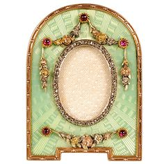 """A Faberge gem-set, gold, and guilloche enamel frame, workmaster Victor Aarne, St. Petersburg, circa 1899-1908, with scratched inventory number 5975. The domed frame on bracket feet enameled in pale translucent green enamel over a radiating engine-turned ground, the mine-cut diamond oval aperture surrounded by applied three-color gold chased floral swags and cascades accented by cabochon rubies. Mother of pearl back with hinged scrolling gilt strut.   Height: 1 5/8""""."""
