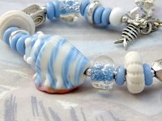 This bracelet is like a beach vacation! Love the shell lampwork bead and the little fish!