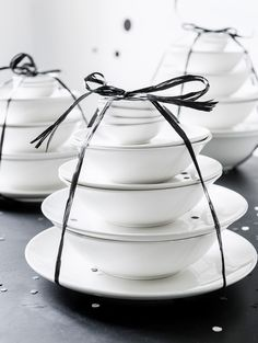 Black and white table setting of white tableware, plates, and bowls, with a black bow and confetti at a dinner party | Styling Kim Rossenberg | Photographer Sjoerd Eickmans | vtwonen may 2015 | #vtwonencollectie