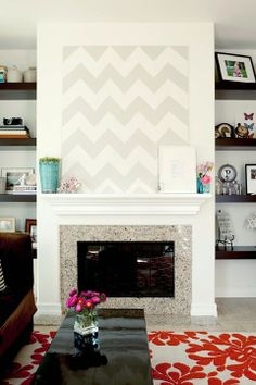 modern chevron painting above fireplace mantle - also love the minimalist espresso dark wood shelves