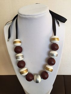 Thirteen medium-size wooden beads hand-painted maroon, white, silver and gold. Placed on a black ribbon that can be adjusted to various lengths.