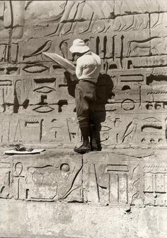 Tourist, interested in cuneiform writing, is copying Egyptian hieroglyphs from the walls of old Egyptian monuments. 1927