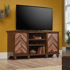 Accommodates up to a 60 in. TV weighing 95 lbs. or less. Two adjustable shelves hold audio/video equipment. Doors feature chevron wood block pattern. Adjustable shelf behind each door. Detailing includes solid wood, turned feet. Quick and easy assembly with patented slide-on moldings. Curado Cherry finish.