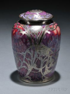 Ruskin Pottery Silver Overlay Covered Jar  Art pottery and silver  England, early 20th century  Circular top pierced for aromatic ventilation, cover and base in purple-red crystalline glaze with fine silver overlay of flowers and vines, pottery marked on base, Ruskin pottery 1908,- lovely