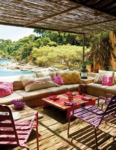 al fresco dining amidst pops of pink and orange pillows with lounge chairs and a shady overhang.. perfect tropical party ingredients.