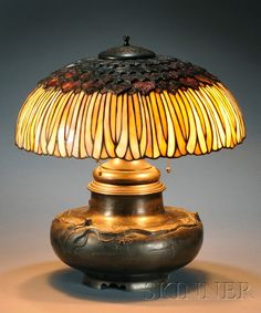 , MOSAIC SLAG GLASS AND BRONZE TABLE LAMP, , PIERCED BRONZE HEAT CAP OVER DOMED SHADE COMPOSED OF GOLD, BROWN, BLUE, AND OPALESCENT WHI - 20TH CENTURY FURNITURE & DECORATIVE ARTS - SALE 2531B - LOT 301 - Skinner Inc