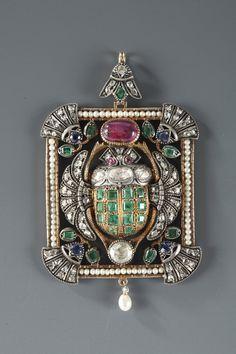 Pendentif en or 14 k et argent, à décor de scarabée ailé, le corps orné d'émeraudes calibrées et de roses couronnées, surmonté d'un rubis cabochon, dans un encadrement...