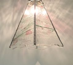 This charming stained glass pendant light has an airy feel and features dainty spring colors of pink and green on a clear textured glass base.