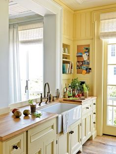 Airy coastal cottage kitchen with yellow painted walls and cabinets