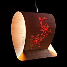 Lampara de madera, al iluminarse puede verse dibujos labrados en el interior y con su luz apagada es simplemente una lámina de madera.