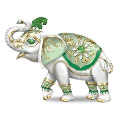Good fortune shines on in elephant figurine with upturned trunk; golden filigree; ornate gems; pearlescent glaze; and real feather. Limited edition.