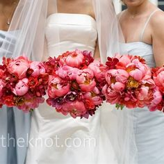 The bridesmaids all carried monochromatic bouquets matching the bride's bouquet of coral peonies and ranunculus, red mokara orchids, and lisianthus. A few red cymbidium orchids made the bridal bouquet stand out from the rest.