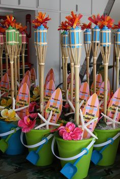 Beach party favors completed with DIY tiki torches in a beach bucket