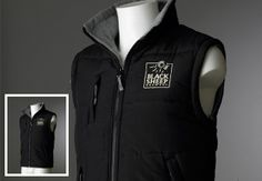 Black Sheep Body Warmer. Luxury black body warmer with grey fleece lining, concealed hood with elasticated draw cord. Two front pockets and a chest zipper pocket. Black Sheep logo embroidered in Silver to the left breast.