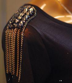 Camiseta com ombro trabalhado com spikes e correntes.