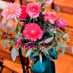 Wrought-iron stands with glass vases of hot-pink flowers stood at the end of some ceremony pews.