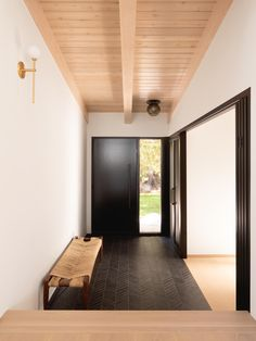 This modern entryway shows off a light wood ceiling, while the floor is a black tile with a chevron pattern.