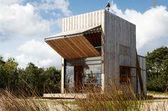 Dieses besondere Haus steht am Strand von Neuseeland. Wenn die Fenster zugeklappt sind, sieht es aus wie eine unauffällige Holzkiste und keiner vermutet, dass es Platz für eine fünfköpfige Familie bietet. Wenn die Holzfassade hochgeklappt wird, sieht man d
