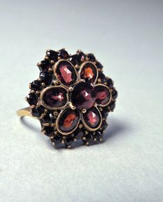 """Beautiful antique Bohemian garnet ring features a centerpiece of faceted garnets in a flower design surrounded by smaller garnet cut stones. This ring appears to be converted from a former life as either a pin or stick pin. The front of the piece is made of gold plating over a silver base. The shank of the ring is made of solid 10k gold and is stamped """"10k"""" plus some letters that are worn. The back of the setting has a cartouche stamped """"Czechoslovakia"""" which dates this piece to between…"""