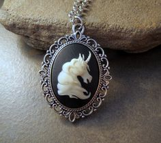 """A nicely detailed unicorn cameo is set into a pretty antiqued silver Victorian setting. The pendant is suspended from a very nice quality silver chain with a matching clasp. Measures: 18"""" long. Pendan"""