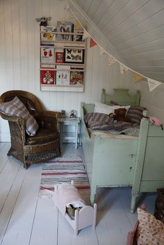 Neat old furniture and painted wood floors in an attic bedroom for a child.