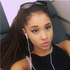 Ariana Grande posing with white headphones in and black sunglasses on her head. She is wearing a white bra and black tank top.
