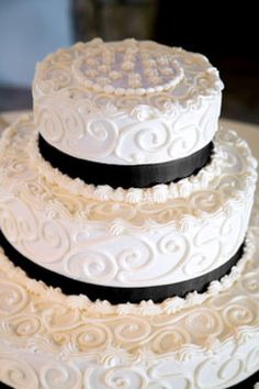 Round three tiered white and black wedding cake with lot of decorative buttercream scrolls.