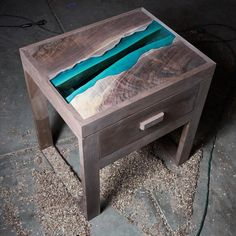 The Granite Creek Nightstand. The design features a figured black walnut top and a half inch thick glass river. I will do a video of the finish application soon!