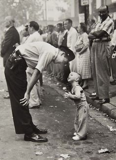 1958 by William C. Beall. This picture of a helpful policeman won a Pulitzer Prize.  Actually the cop was politely asking the kid to leave the path of a parade.