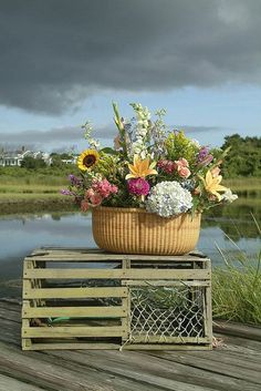 Nantucket inspired arrangement with a basket of fresh flowers placed atop a lobster trap.