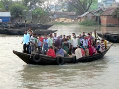 Heavily loaded passenger boats cross the Rupsa River at Khulna, Bangladesh.