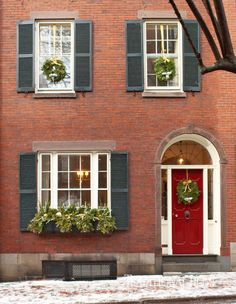 This charming Beacon Hill home evokes a traditional Christmas mood thanks to charming wreaths and fresh greenery in the window box. - Photo: Michael Partenio