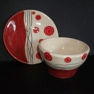 """This set comprises of a small plate and bowl made from white earthenware clay and decorated with a red and black abstract pattern. The plate is saucer sized and measures 6"""" diameter or 15cm The bowl measures 4.5"""" diameter and 3"""" deep or ..."""