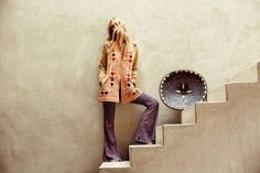 Marloes Horst poses on stairs while modeling an embroidered jacket and flared pants