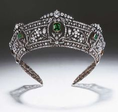 The Harcourt Tiara  Emeralds and diamonds  - seven graduated step-cut emeralds set within sprays of diamond flowerheads and leaves, running between borders of continuous diamond collets and ribbon motifs, mounted in silver and gold, circa 1900