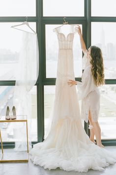 """From the editorial """"Two Broadway Actors Tie The Knot At The Coolest Brooklyn Venue!"""" On SMP you can browse through the full gallery captured by LBB photographer @rebeccayale and see more of this wedding's stunning greenery, contemporary decor details, and New York City skyline view! 💫 #bride #weddingdress #bride #newyorkwedding #skyline #weddingphoto #weddingphotoidea Fit And Flare Wedding Dress, Luxury Wedding Dress, Wedding Gowns, Wedding Picture Poses, Wedding Photos, Bridesmaid Robes, Bridal Robes, Long Sleeve Wedding, Wedding Photo Inspiration"""