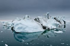 An iceberg in the Ilulissat Fjord appears sculpted by wind and water.