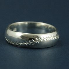 MATERIAL: 925 Sterling Silver -->WIDTH: 6mm Wide by 2mm Thick  America's Pastime pays homage to our nations most beloved sport. This Sterling Silver band is expertly engraved in our studio with a hand-cut baseball thread pattern. The band measures 6mm by 2mm in sterling silver. Customize your selection with your choice of finish: High Polished or Brushed. Tastefully display your affinity for Americas greatest game!  Want the baseball thread to really stand out? Check out the Americas Past...